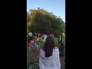Girl catches wedding bouquet and celebrates whilst her boyfriend holds his head