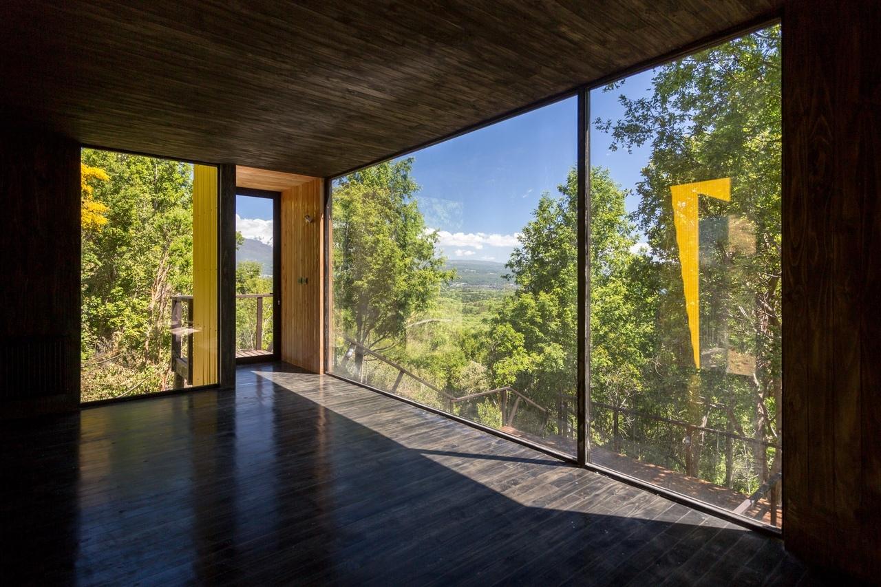 Сборный жилой дом, с фасадами желтого цвета среди чилийских гор.