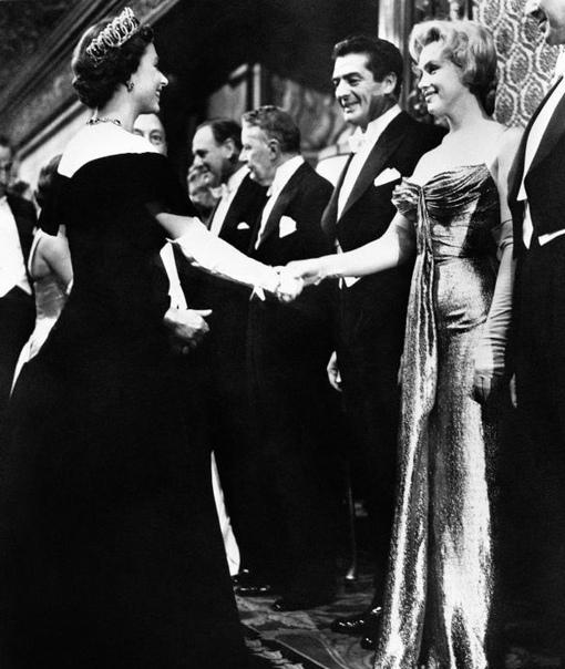 """Английская королева Елизавета II пожимает руку своей ровеснице, американской актрисе Мэрилин Монро на премьере фильма """"Битва у Ла-Платы""""."""